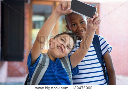 Happy classmates taking selfie at school corridor