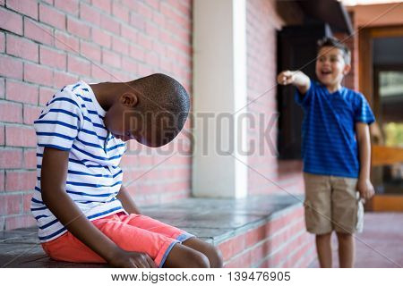 Boy laughing on sad classmate in corridor at school
