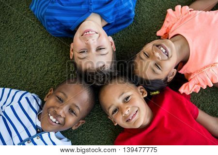 High angle portrait of happy children forming huddle at park
