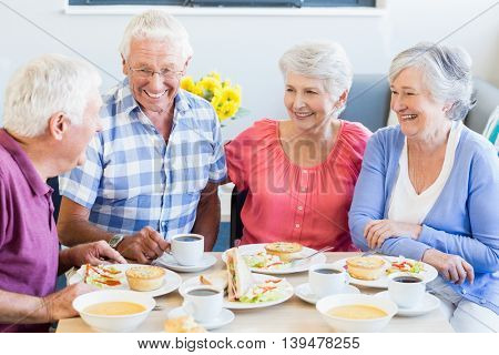Seniors having lunch together in a retirement home poster