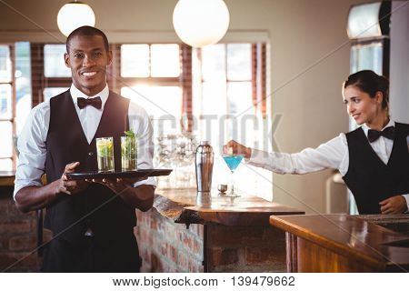 Portrait of bartender holding a serving tray with two cocktail glass