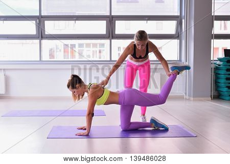 Personal trainer helping girl in stretching workout at gym fitness, yoga pose Sunbird .