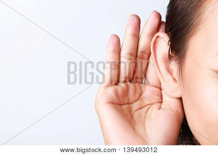 Listening female holds his hand near her ear on white background