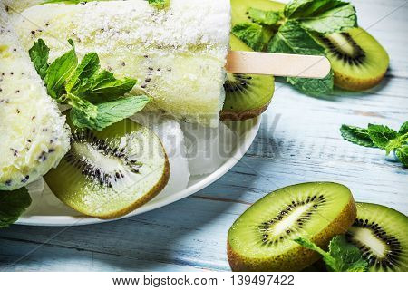 Homemade popsicles with kiwi and mint on a wooden table. Focus on the top popsicles