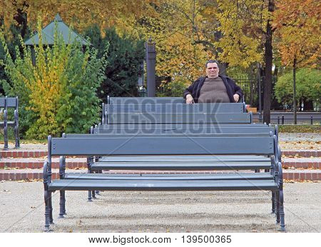 Warsaw, Poland - October 23, 2015: fat man is sitting on a bench in park of Warsaw, Poland