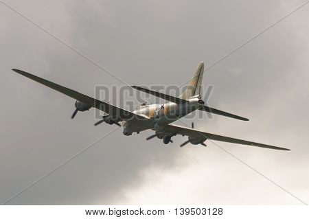 FARNBOROUGH, UK - JULY 17: Vintage Boeing B-17 Flying Fortress bomber in cloudy skies over Farnborough, UK on July 17, 2016