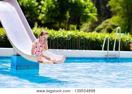 Happy laughing little girl playing on water slide in outdoor swimming pool on hot summer day. Kids learn to swim. Child wearing sun protection rash guard sliding on aqua playground in tropical resort