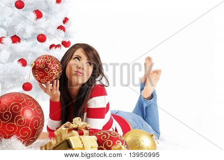 young woman with gift box next to white christmas tree