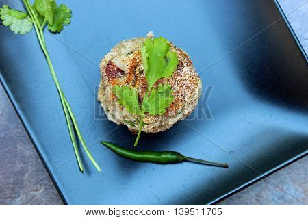Colocasia or taro root or yam cutlet made with boiled colocasia mixed with onions and herbs with copy space.