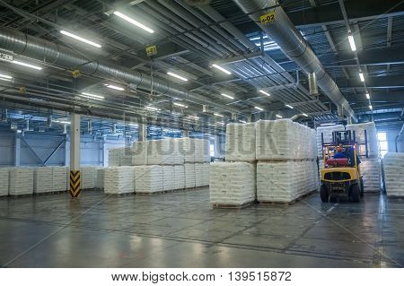 Tobolsk, Russia - July 15. 2016: Sibur company. Central control panel of Tobolsk Polymer plant. Driver on forklift truck loads pallets with finished goods from packaging machine