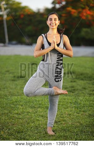 Youthful woman performing yoga in the park