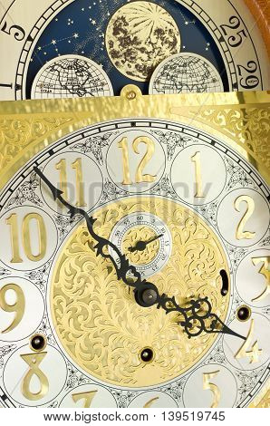 ornate brass engraved grandfather clock face with arabic numerals and moon phase dial