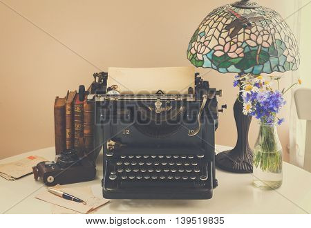 black vintage typewriter with books on wooden table with art nuveau lamp, retro toned