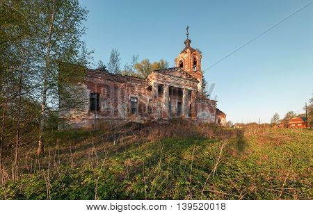 Abandoned brick orthodox church with a portico and columns at sunset