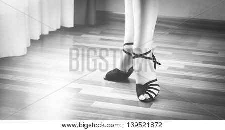 Female ballroom standard sport dance latin and salsa dancer feet and shoes in dance academy school rehearsal room dancing salsa.
