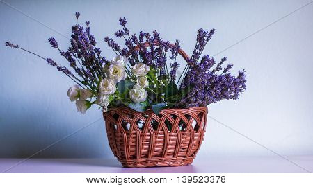 Lavender and white rose in brown creel