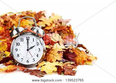 Alram clock in colorful autumn leaves isolated against a white background with light shadow and shallow depth of field. Daylight savings time concept.