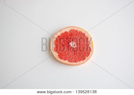One Slice Of Red Grapefruit On A Light Background