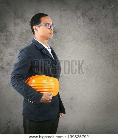 portrait of self conficence engineering man holding safety helmet against cement wall