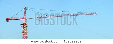 Red and white building tower crane against a blue sky. Jib crane