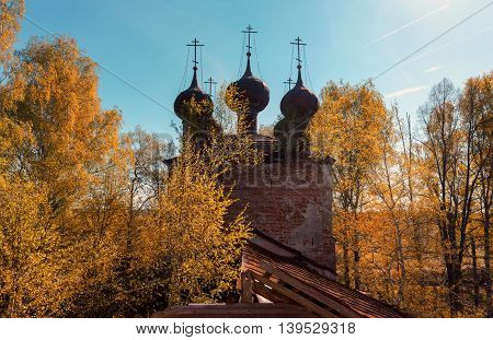 Silhouette five-domed quadrangle abandoned russian temple. Against the background of an autumn forest