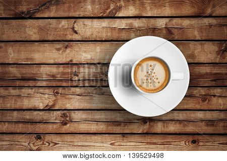 top of view of great italian espresso coffee in a white cup on wood table with foam tree christmas shape