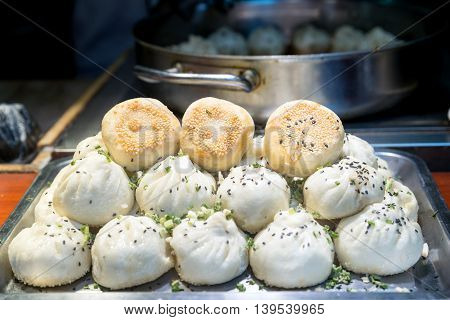 Fried Chinese pork bun in food market Shanghai China. Tradition Shanghai Chinese food.