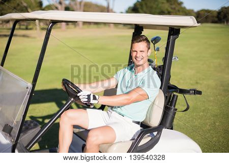 Portrait of happy golfer man driving golf buggy on field