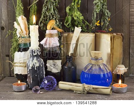 Homeopathic still life with candle, vintage bottles, healing herbs, book and old paper scrolls, alternative medicine concept