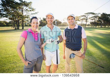 Portrait of smiling golfer friends standing on field