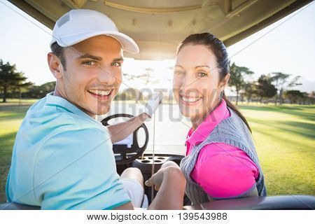Portrait of cheerful golfer couple sitting in golf bugggy