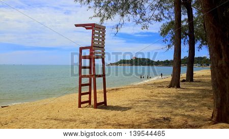 red and white wooden slat lifeguard stand on the beach under pine trees on the right, distant swimmers playing in the sea, peninsula seen in the distant background, Songkhla, Thailand