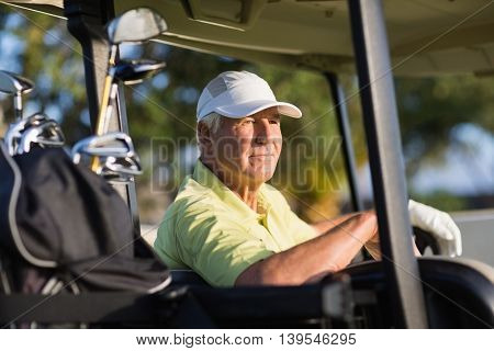 Thoughtful golfer man looking away while sitting in golf buggy