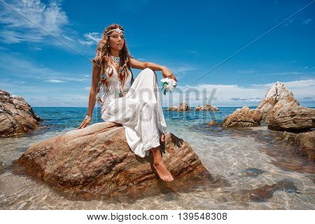 Beautiful young bride in white wedding dress on beach