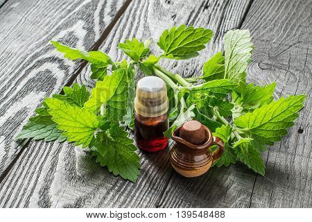 Essential oil melissa officinalis in a small brown bottle and small clay jar fresh melissa on a dark wooden table