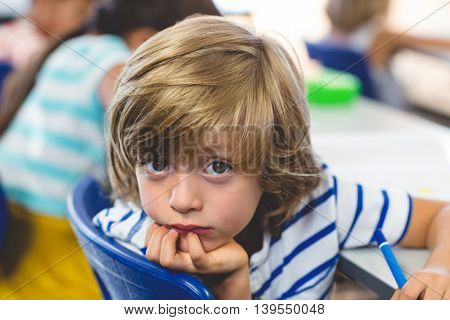 Close-up portrait of serious boy with classmates in classroom