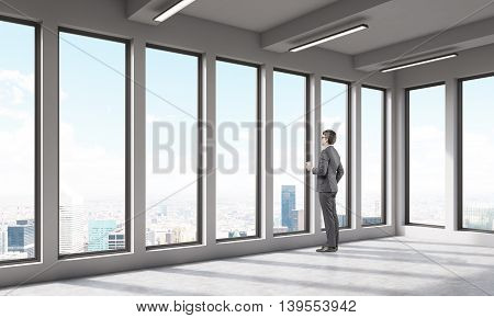 Man in empty office room looking at big city through large window. Concept of thoughtfullness. 3D render.