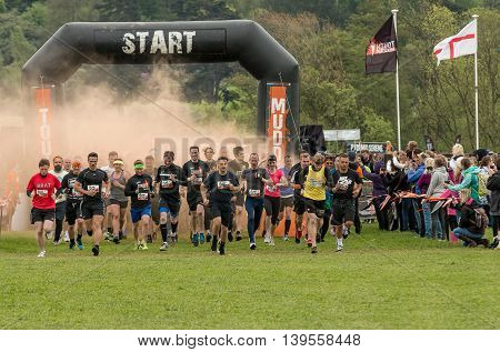 Grantham Leicestershire/UK - May 21, 2016: Tough Mudder participants kick off at the start line through the orange smoke taking on the 2016 Tough Mudder extreme sports charity competition at Belvoir Castle.