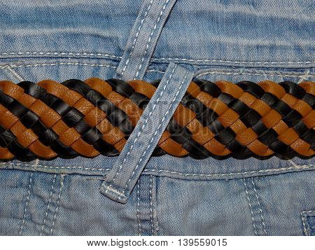 light blue denim fabric sewn into her seams and leather belt close-up