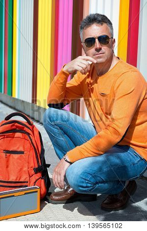 Street fashion. Male outdoor portrait. Man sitting near colored wall in jeans, orange sweater with backpack.