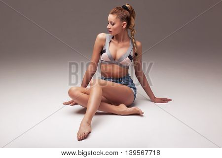 sexy woman in shorts and lingerie on a gray gradient background aroused body