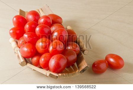 Vegetable Organic Grape Tomatoes or Cherry Tomatoes on A Small Wooden Boat.