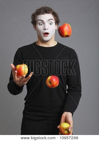 Portrait of Mime with red apple on grey background