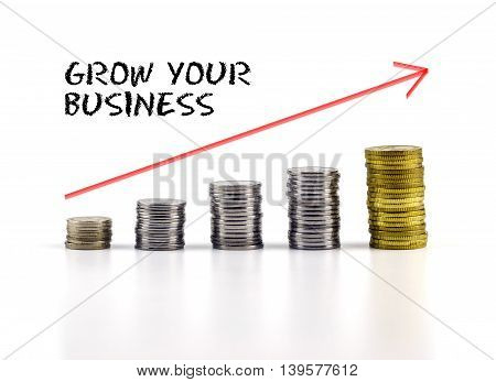 Conceptual Image. Stacks Of Coins Against White Background With Red Arrow And Grow Your Business Wor