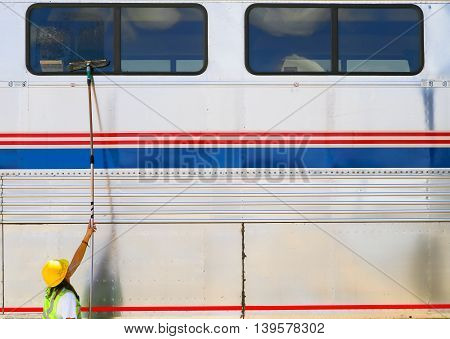 ALBUQUERQUE, USA - MAY 24, 2015: A worker is cleaning the windows of a bilevel car of the Amtrak passenger train Southwest Chief at the station.