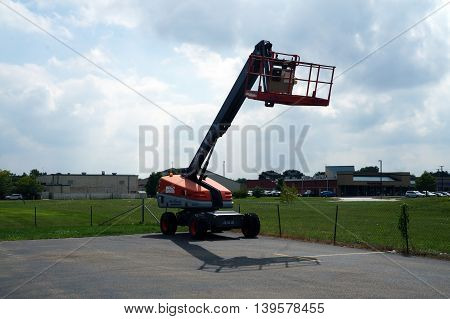 SHOREWOOD, ILLINOIS / UNITED STATES - AUGUST 30, 2015: A Skyjack SJ45T Boom Lift sits parked in a corner of a parking lot.