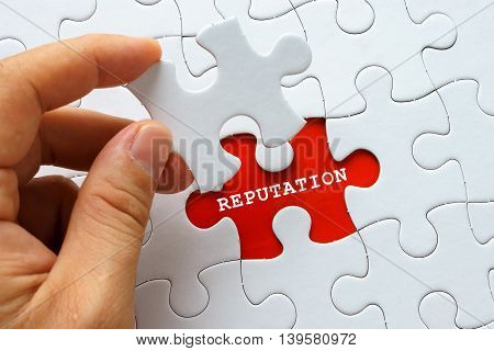 Hand holding a piece of white puzzle with word REPUTATION