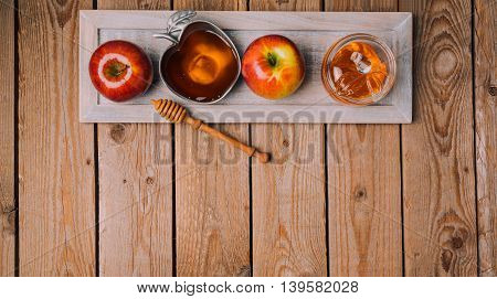 Rosh Hashana holiday background with honey and apples on wooden table. View from above. Flat lay