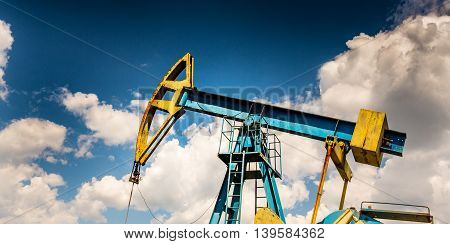 Oil and gas well profiled on blue sky with cumulus clouds