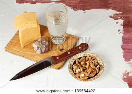 Grunge food. Still life with cheese garlic walnuts and mineral water.